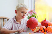 Happy boy carving pumpkin for halloween — Stock Photo