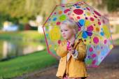 Portrait of little girl with colourful umbrella — Stock Photo