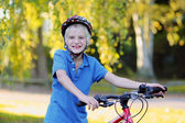 Happy school boy riding bike in park — Stock fotografie