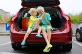 Brother and sister sitting in trunk after shopping — Стоковое фото