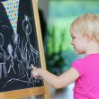 Little girl drawing on black board — Stock Photo #56129675