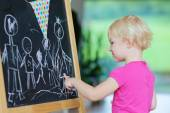 Little girl drawing on black board — Stock Photo