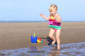 Happy little girl playing on the beach — Stock Photo