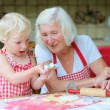Grandmother making cookies with her granddaughter — Stock Photo #57103573