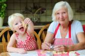 Grandmother making cookies with her granddaughter — Stock Photo