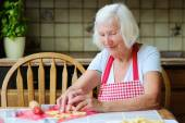 Happy grandmother making tasty cookies at kitchen — Stock Photo