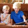 Brother and sister playing with tablet pc on sofa — Zdjęcie stockowe #57211261