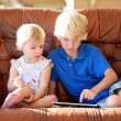 Brother and sister playing with tablet pc on sofa — Zdjęcie stockowe #57211275