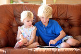 Brother and sister playing with tablet pc on sofa — Stock Photo