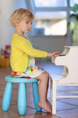 Little girl playing piano toy at home — Stock Photo