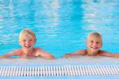 Two boys having fun at summer swimming pool — Stock Photo