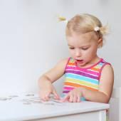 Toddler girl assembling jigsaw puzzle — Stock Photo