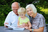 Grandparents with grandchild looking family photo album — Stock Photo