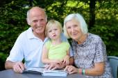 Grandparents with grandchild looking family photo album — Foto Stock