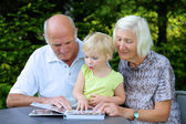 Grandparents with grandchild looking family photo album — Stockfoto