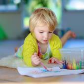 Small girl drawing on paper lying on the floor — Stock Photo