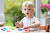 Toddler girl making plasticine cookies — Stock Photo