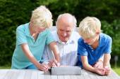 Grandkids teaching grandpa to use tablet pc — Photo