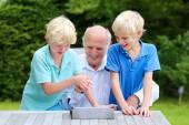 Grandkids teaching grandpa to use tablet pc — Stock Photo