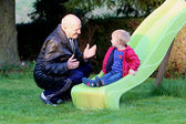 Grandfather and granddaughter in playground — Foto de Stock