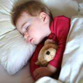 Toddler girl sleeping in bed with teddy bear — Stock Photo