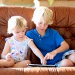 Brother and sister playing with tablet pc — Zdjęcie stockowe #60357375