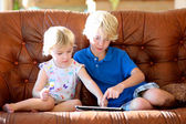 Brother and sister playing with tablet pc — Stock Photo
