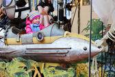 Little girl enjoying merry-go-round — Stock Photo