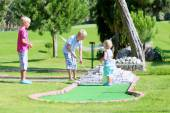 Group of kids playing mini golf outdoors — Stock Photo