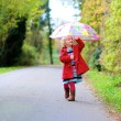 Happy preschooler girl walking with umbrella — Stock Photo #62561313