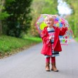 Happy preschooler girl walking with umbrella — Stock Photo #62561337