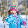 Little girl playing at winter forest — Stock Photo #62561483