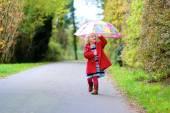 Happy preschooler girl walking with umbrella — Stock Photo