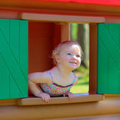 Happy little girl hiding at playhouse — Stock Photo
