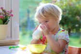 Toddler girl drinking milk from glass — Stock Photo