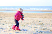 Little girl playing on the beach at winter — Stock Photo