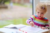 Toddler girl drawing at school or home — Stock Photo