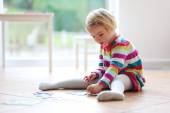 Preschooler girl playing with jigsaw puzzle — Stock Photo
