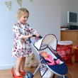 Cute little girl playing with toy pram and doll — Stock Photo #64405829