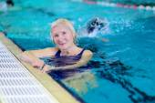Senior woman enjoying lesson in swimming pool — Stock Photo