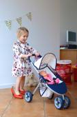 Cute little girl playing with toy pram and doll — Stock Photo