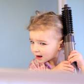 Happy little girl brushing and styling her hair — Foto de Stock