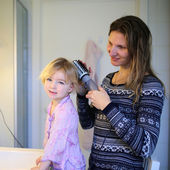 Mother and little daughter brushing hair using styler — Stock Photo