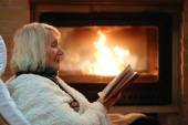 Senior lady relaxing at home by fireplace — Stock Photo