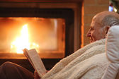 Senior man relaxing at home by fireplace — Stock Photo