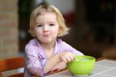 Blonde little girl eating muesli with yoghurt for breakfast — Stock Photo