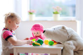 Preschooler girl playing with plastic toys vegetables — Stock Photo