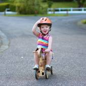 Little girl riding tricycle on the street — Foto Stock