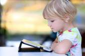 Preschooler girl playing with tablet pc — Stock Photo