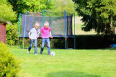 Two brothers playing soccer in the garden — Stock Photo